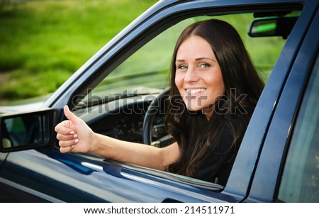 Young and beautiful lady showing thumb-up from her older used car - stock photo