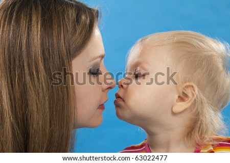Young and beautiful mother with her sweet little daughter isolated on blue.