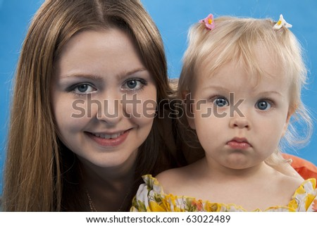 Young and beautiful mother with her sweet little daughter isolated on blue. - stock photo