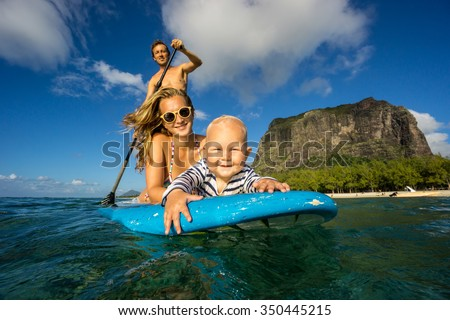 Young and beautiful parents ride by surfboard with baby in the Indian Ocean island of Mauritius on the background of mountains. They surf on a paddle board in transparent waters.  - stock photo
