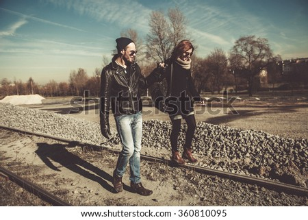 Young and beautiful rock and roll couple walking outdoors on a sunny day - stock photo