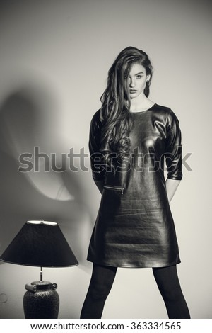 Young and beautiful seductive woman in a black vinyl/leather dress,black tights and shoes - stock photo