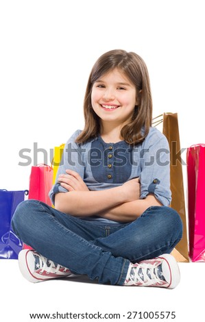 Young and beautiful shopping girl sitting with shopping bags on white background - stock photo
