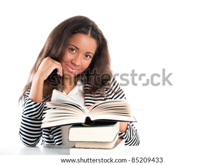 Young and beautiful smiling student with open books doing homework on a desk