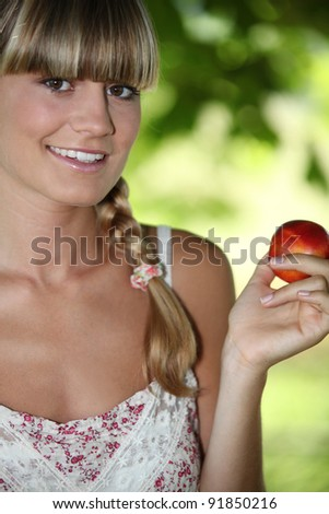 Young and beautiful woman holding a nectarine