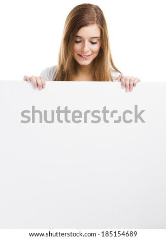 Young and beautiful woman holding and looking to a big blank board, isolated over white background