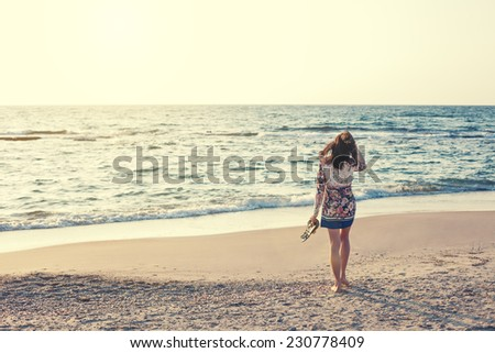 young and beautiful woman in colorful dress walking on the beach near the ocean and looking far away at the sunset - stock photo