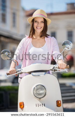 Young and beautiful woman in nifty hat riding scooter. - stock photo