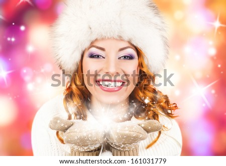 Young and beautiful woman in traditional winter dress over abstract Christmas background - stock photo