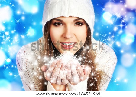 Young and beautiful woman in traditional winter dress over blue background - stock photo