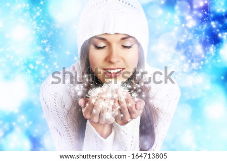 Young and beautiful woman in traditional winter dress over blue background