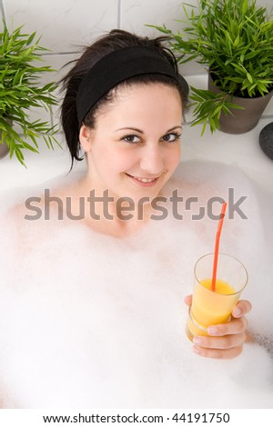 Young and beautiful woman is having a drink  in the bathtub - stock photo