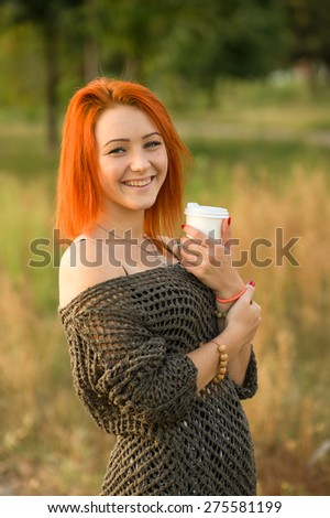 Young and beautiful woman on the background of nature city park. Woman drinking tea or coffee from a white paper disposable cup. Concept - tea or coffee cup. Reddish hair girl walk in the park. - stock photo