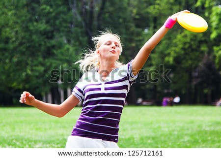 young and beautiful woman playing frisbee in the park - stock photo