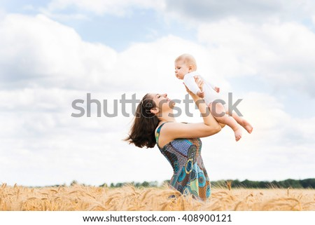 Young and beautiful woman playing with her infant baby in a meadow of wheat. Summer concept. - stock photo