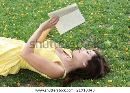 Young and beautiful woman reading her book laying on the grass