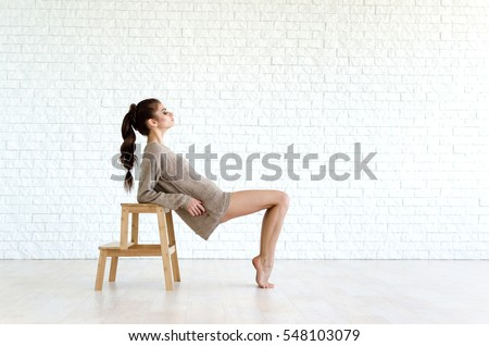 Young and beautiful woman sits on the wooden chair. She is wearing in knitted sweater. Photo is very tender and cozy.