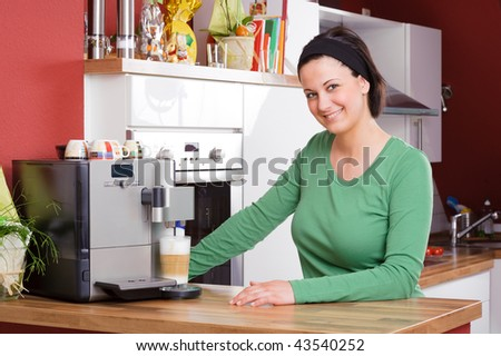 Young and beautiful woman standing in the kitchen beside a coffee machine - stock photo