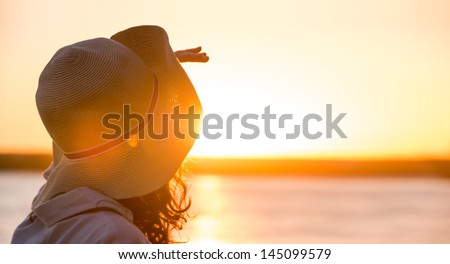 Young and beautiful woman wearing a hat in sunset light looking far away. Photo from behind - stock photo