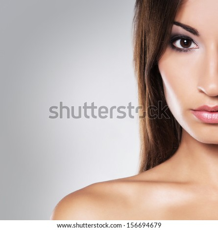 Young and beautiful woman with long brown hair posing over grey background