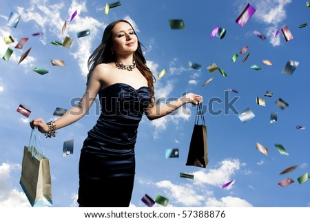young and beautiful woman with shopping bags and raining credit cards - stock photo
