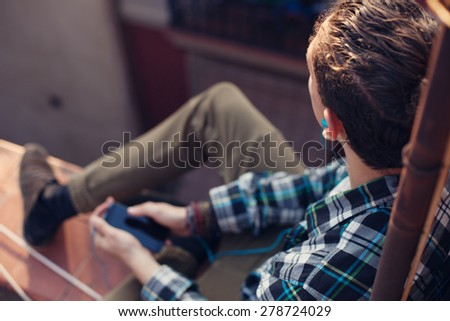 Young and brave traveler man sitting on the roof and listening music on his mobile phone - stock photo