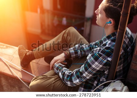 Young and brave traveler sitting on edge of the roof and listening music (intentional sun glare) - stock photo