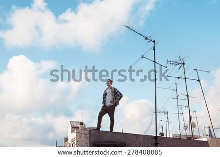 Young and brave traveling man standing on the roof, smiling and looking far away with bright blue sky and white clouds and antennas - stock photo