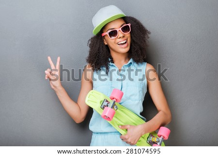 Young and carefree. Attractive young African woman holding colorful skateboard and smiling while standing against grey background  - stock photo