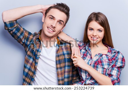 Young and carefree. Beautiful young loving couple smiling while standing against grey background  - stock photo
