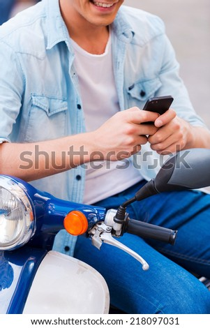 Young and carefree. Close-up of young man sitting on scooter and typing something on his mobile phone   - stock photo