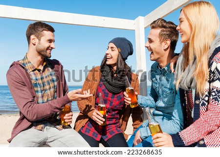 Young and carefree. Four happy friends talking to each other and smiling while sitting on the beach and drinking beer  - stock photo