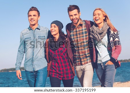 Young and carefree. Four young happy people bonding to each other and smiling while walking by the beach together - stock photo