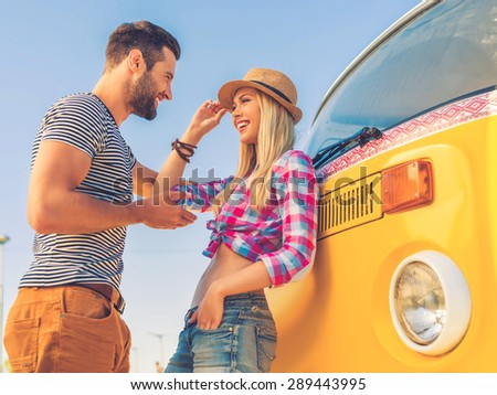 Young and carefree. Low angle view of beautiful young couple talking to each other and smiling while leaning at their retro minivan - stock photo