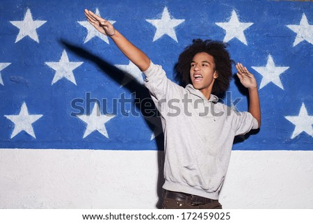 Young and carefree. Young African man posing against American flag and gesturing - stock photo