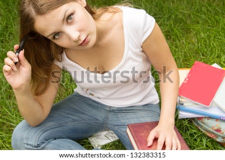 Young and charming woman with long hair, holding book, thinking and looking into the camera - stock photo