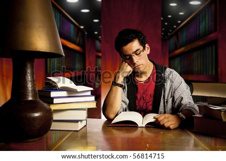 young and concentrated student reads a book - stock photo