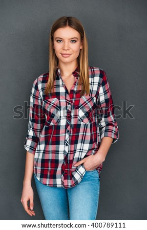 Young and confident. Beautiful young woman keeping hand in pocket and looking at camera with smile while standing against grey background - stock photo
