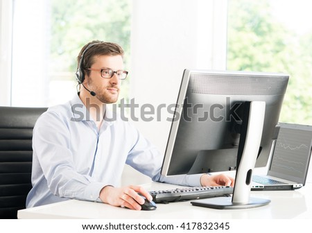 Young and confident customer support operator working in a call center office - stock photo