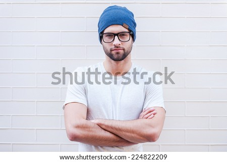 Young and creative. Handsome young man in eyeglasses keeping arms crossed and looking at camera while standing against brick wall  - stock photo