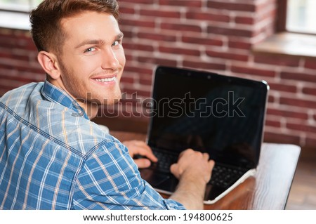 Young and creative. Rear view of handsome young man working on laptop and looking over shoulder while sitting at his working place  - stock photo