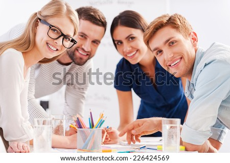 Young and creative team. Four cheerful business people in smart casual wear discussing something and smiling while leaning at the table - stock photo