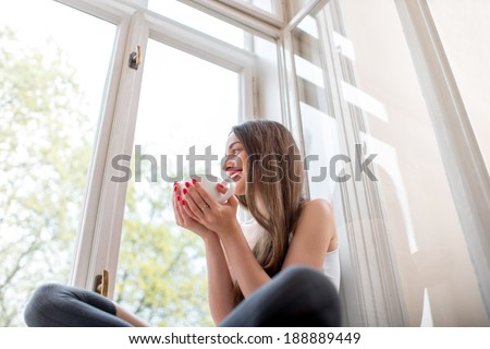 Young and cute lady sitting on the windowsill and looking out the window with cup of coffee in the morning - stock photo