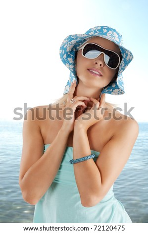 young and cute woman with sunglasses pushing hat against head - stock photo