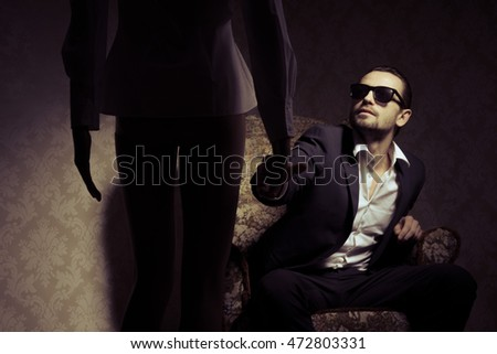 Young and elegant man sitting in chair wearing black suit, white shirt and sunglasses looking at woman standing in front of him isolated over vintage wall background
