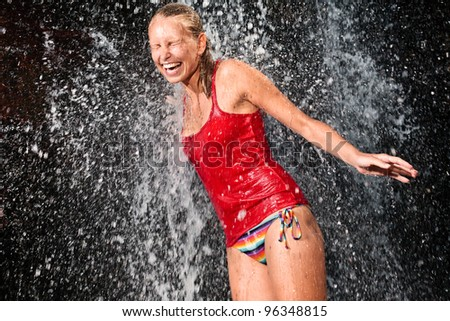 Young and emotional girl in red tank-top enjoying jungle waterfall - stock photo