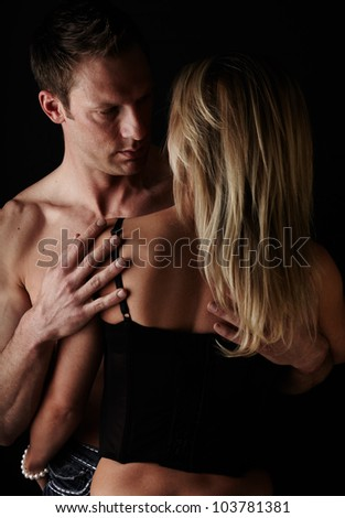 Young and fit caucasian adult couple in an embrace. Semi-nude and topless against a dark background with the woman wearing a sexy red and black lace corset.. - stock photo