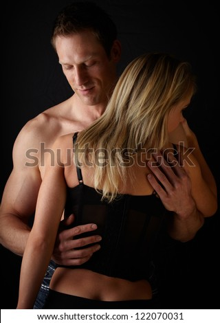 Young and fit caucasian adult couple in an embrace. Semi-nude and topless against a dark background with the woman wearing a sexy red and black lace corset..