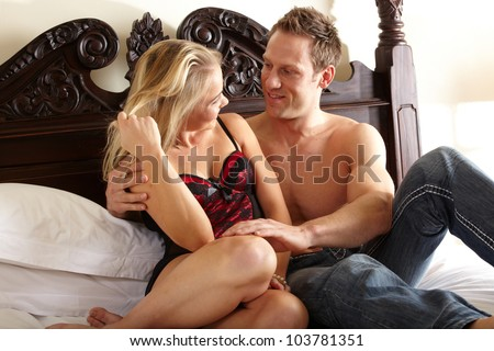 Young and fit caucasian adult couple in an embrace. Semi-nude and topless on a bed in a light bedroom with the woman wearing a sexy red and black lace corset and the man wearing only blue jeans.