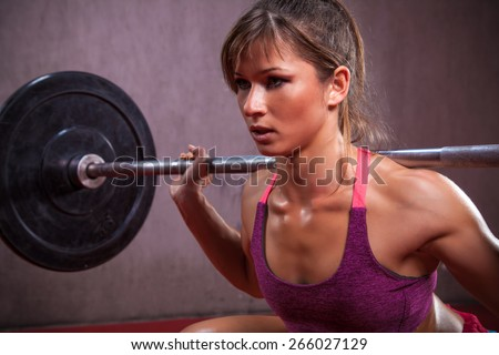 Young and fit female athlete performed squats in the gym. - stock photo